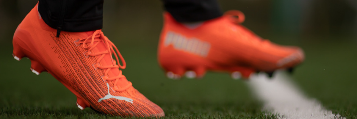 Football player wears firm ground football boots on dry, hard pitch