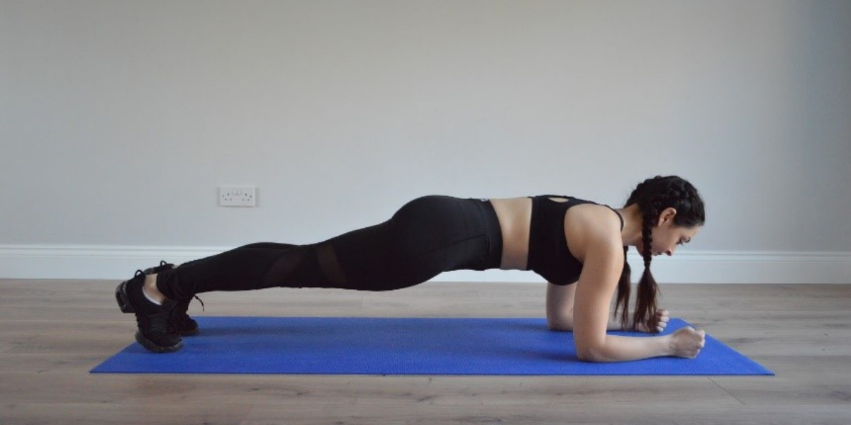 fitness model performing plank position working out at home on yoga mat